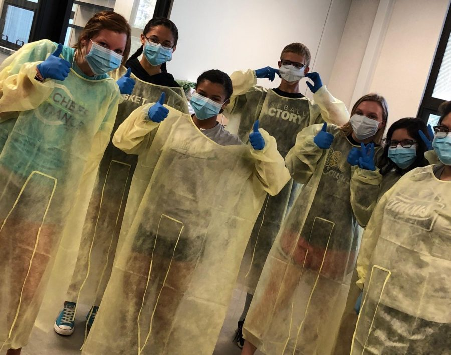 Students+learn+the+proper+way+to+put+on+CNA+gowns%2C+gloves+and+masks.