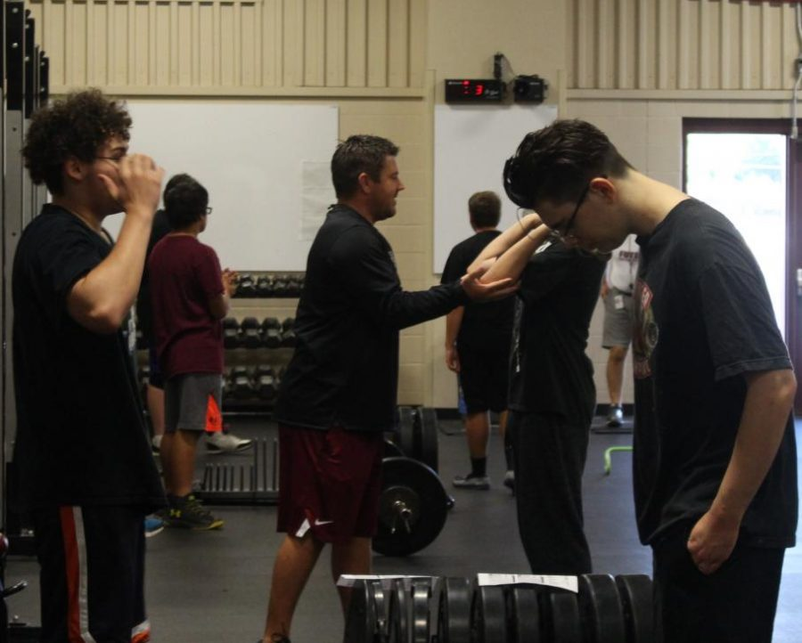 Coach+Sandbo+teaching+a+student+how+to+lift+the+weights+properly%2C+without+injuring+himself+or+others.