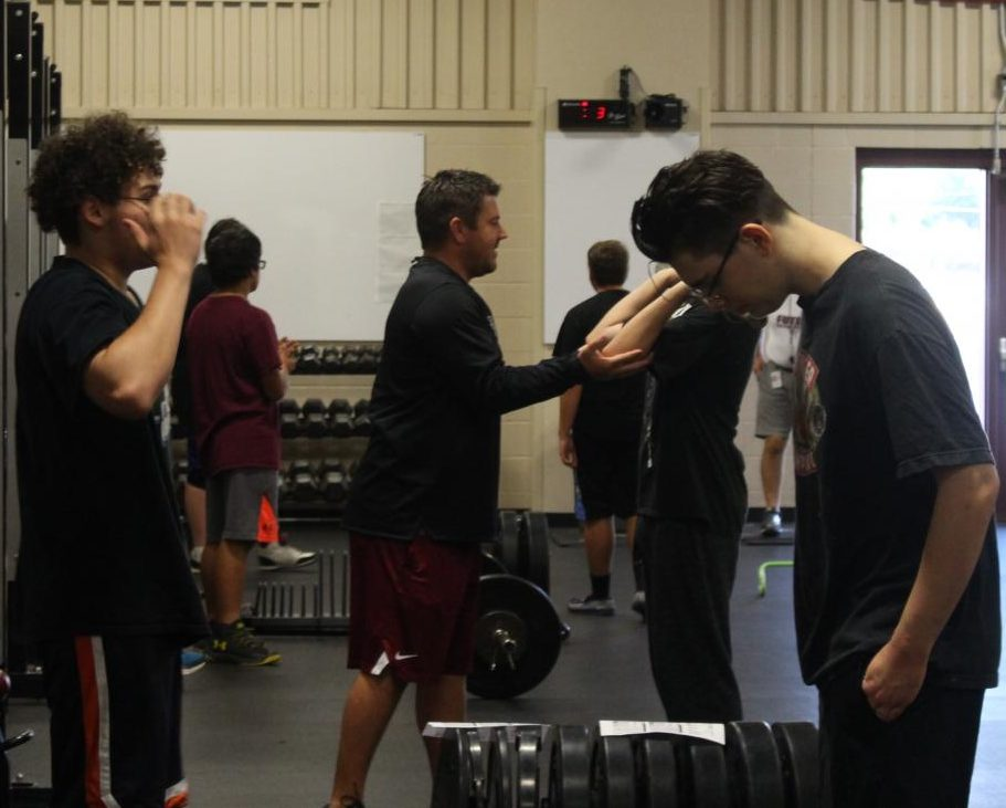 Coach Sandbo teaching a student how to lift the weights properly, without injuring himself or others.
